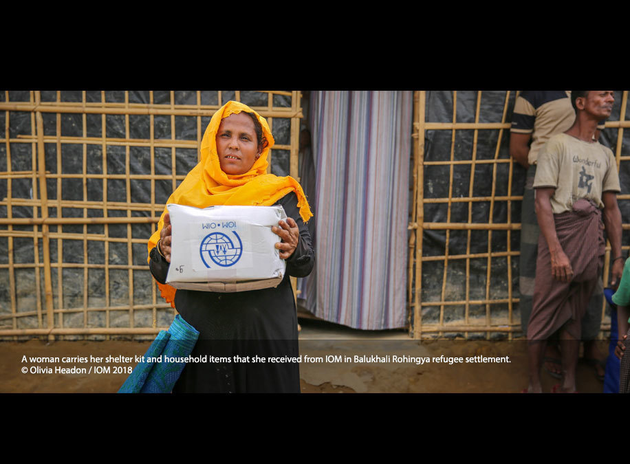 A woman carries her shelter kit and household items that she received from IOM in Balukhali Rohingya refugee settlement.