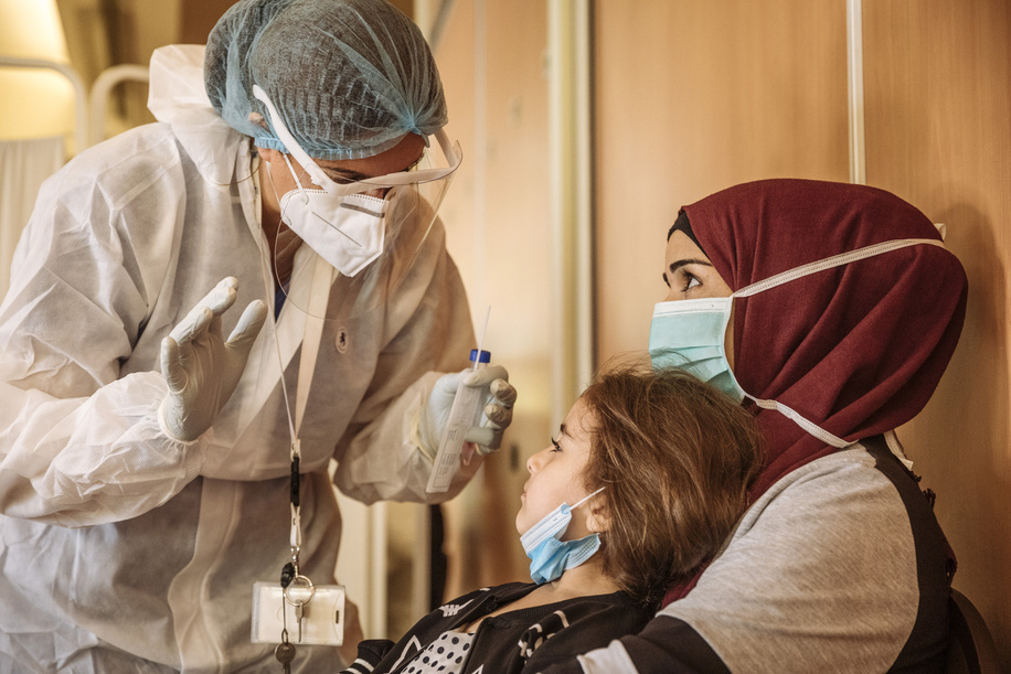 Syrian refugees undergo a PCR test for COVID-19 with IOM staff three days ahead of their scheduled resettlement flight to Europe. During the current pandemic, IOM has adapted operations and safety procedures to ensure that all refugees are screened for COVID prior to their flight and can quarantine in hotels with their families as their await results before travelling.