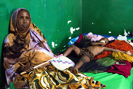 MSO0048  A mother at the public hospital sits next to her son who is delirious with snakebite. She only has a fan to cool him down from harsh 45 degree heat. Migrants and internally displaced persons (IDP) are among the poorest and most vulnerable in Bossaso, Somalia.