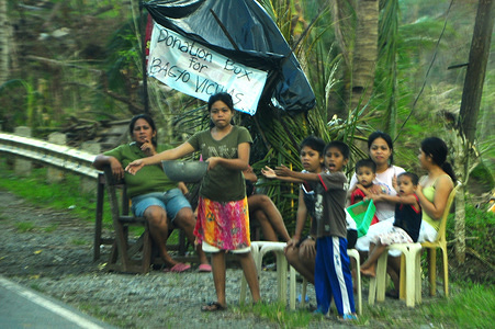 After Typhoon Bopha left the Philippines, the scale of destruction only become clear with tens of thousands homeless and hundreds still missing. Typhoon victims are seen along the roadside begging for assistance. .