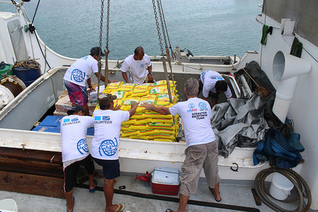 """Locally sourced rice, funded by USAID, being loaded onto the""""Indies Trader"""" for onward transport to Maloelap Atoll, a 16-hour sea voyage away. A severe drought left remote island communities short of essential foodstuff. © IOM/Joe Lowry 2013"""