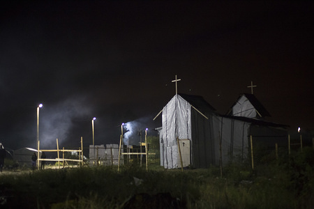 The church is closed at night. Most of the worshipers are Eritreans and Ethiopians. A mass is held inside its plastic walls every Sunday. Faith is a very important part of many of those who now call this place their home, albeit a temporary one, as many of them hope. © IOM/Amanda Nero 2015  At night, the 'New Jungle', the informal migrant and refugee settlement in the port city of Calais, France, comes to life. Several improvised bars, restaurants and shops open after sunset. Its residents gather together to dance, play games, drink and eat. Some make bonfires and chat outside, others play football, and traditional music floats in the air.
