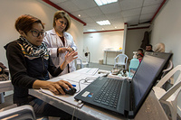 An IOM staff is inputting medical information following an evaluation on a Syrian family.