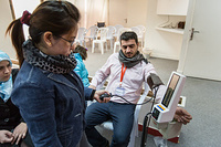 A Syrian family is undergoing medical evaluations to measure their height, weight, and blood pressure before proceeding to meet with an IOM physician for a physical examination.