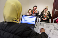 A Syrian family is being asked about their medical history by an IOM physician before undergoing a physical examination.