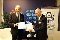 White Helmet Humanitarians: IOM Director General William Lacy Swing and H.E. Carlos Foradoni, Vice-Minister of the Ministry of Foreign Relations and Worship of the Argentina sign an accord at the World Humanitarian Summit.