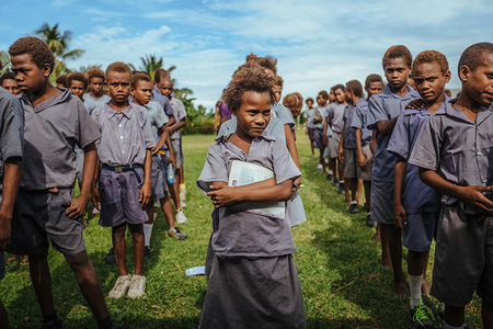 Children at an elementary school in Kokopo line up before attending an awareness raising session led by IOM. The school and its nearby community are located near an active volcano which had a major eruption in 1995 resulting in a major displacement. Since then, a number of communities have returned despite the risk of a future eruption. Photos: IOM 2016 / Muse Mohammed
