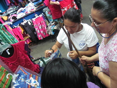 IOM Project Assistant, Tatiana Ortiz, accompanies a beneficiary to make initial purchases for her new clothing business.