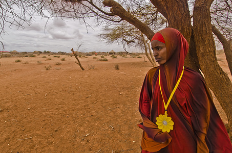 Displaced Somali beneficiary gazes at the horizon wearing the Little Sun solar lamp.