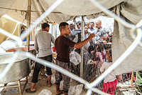 displaced Iraqis from West Mosul in Hammam Al-Alil transition zone wait in line to get food.