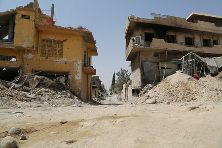 A damaged neighborhood in West Mosul. Destruction and rubble can be seen through the end of the street.
