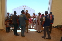 parents of displaced children line up to receive new clothes and toys for their children