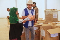 IOM staff distributes clothes and toys to displaced children at Haj Ali emergency site.