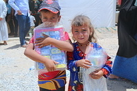 two kids who received clothes and toys