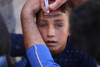 a displaced child and Haj Ali emergency site.