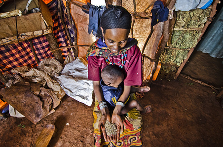 Tia, with her youngest son on her lap, shows the wheat she will be preparing for dinner with the cooking pot she received as part of the emergency shelter and non food item kit. Photo: Rikka Tupaz / UN Migration Agency (IOM) 2017
