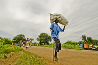 South Sudanese Refuee crossing Pagak border into Ethiopia carrying his belongings.