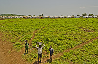 South Sudanese refugee children with view of shelters of Nguenyyiel Refugee Camp.