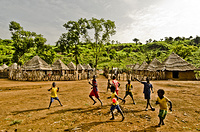 South Sudanese refugee children playing in open space with transitional shelter in background at Kule Refugee Camp.