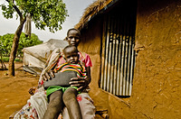 Cholbuol and her two-year old son in front of their transitional shelter at Kule Refugee Camp