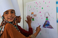 Jehan, left, and Rawnaq, right, go to IOM's psychosocial center at Chamakor camp, to take part in the recreational activities such as drawing. In this picture, the girls worked together to draw and paint this together.