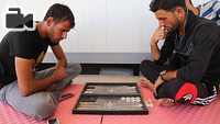 displaced Iraqis play backgammon at IOM's Psychosocial Center in Chamakor Camp, east of Mosul.