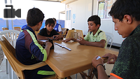 displaced children play dominoes at IOM's Psychosocial Center in Chamakor Camp, east of Mosul.