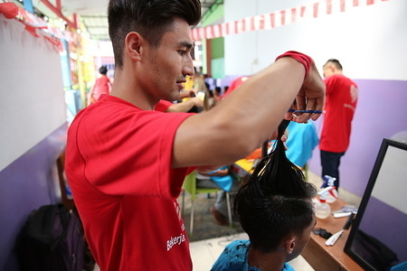 """Refugees from five nations living in Medan, Indonesia with IOM's assistance provided 20 street children and dozens of local residents a special """"spa day"""" treatment prior to the Idul Adha holiday weekend. Fourteen young Afghan, Iraqi, Iranian, Palestinian and Sudanese men who graduated from a three-month hair stylist vocational training program organized by IOM have been volunteering their talents at orphanages and other facilities since mid-2017. They have been living in Indonesia for up to four years awaiting resettlement overseas. Each of the street children, all under the age of 12, received a free hair wash and cut, styling, gel and head massage. They live in the same community as the refugees and receive basic support from volunteers at a local non-profit foundation. More than two dozen youngsters from the area were also tidied up for the holiday."""