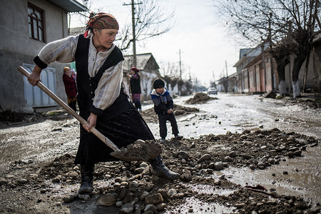 """An elderly woman shovels mud from a destroyed road near her house.   Families left behind is a reality in Central Asia, a region that has more than 10 million migrants on the move looking for better employment and living opportunities beyond the borders of their countries. As migration of both men and women, from Tajikistan, Kyrgyzstan and Uzbekistan, will continue to increase, the number of dependents left behind (children, wives, elderly parents etc.) will rise as well. Migrant workers' families are waiting and barely surviving while their loved ones are trying to make ends meet in Russia and/or Kazakhstan. Many Central Asian children are growing up without seeing their fathers or mothers, or being left behind when both parents are taking the migration route. Currently more and more women are becoming breadwinners as well, changing the sociocultural norms in Central Asia where men were leading the migration numbers. There are also a lot of women, abandoned or divorced, with the task of raising the children on their own and assume the care of elderly parents. """"Your father/mother comes tomorrow"""" is a common phrase that millions of children in Central Asia hear when they ask the questions """"Where is my father? or  Where is my mother? When will he/she come back home""""?   However, no one knows when the """"tomorrow"""" will actually arrive. These children  who will grow up without  regular contact with their  parents will soon be the next generation of adults in the region, making up a  significant part of its  population."""
