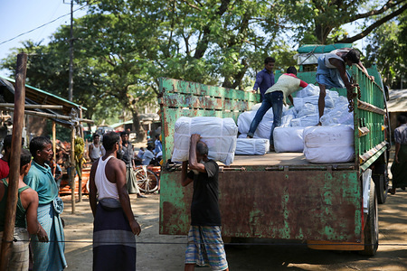 Rohingya refugees working for IOM unload aid items to be distributed to fellow refugees in Balukhali, Cox's Bazar, Bangladesh.
