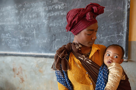 A mother holds with her child in the classroom where they are sheltering. Internal displacement, displacement, IDPs, IDP, Ethiopia, Gedeo, Gedeb, emergency, humanitarian, displaced, internally displaced person, Ethiopia, eastern africa, horn of africa, forced migration, conflict, emergency response, shelter