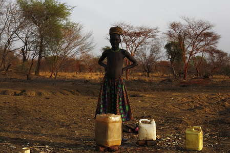 MSD0294 Dinka girl by a puddle where she filled up her jerry cans with unsafe drinking water. Over 500,000 people continue to lack access to improved drinking water in Northern Bahr el Ghazal state. (Malual East payam)